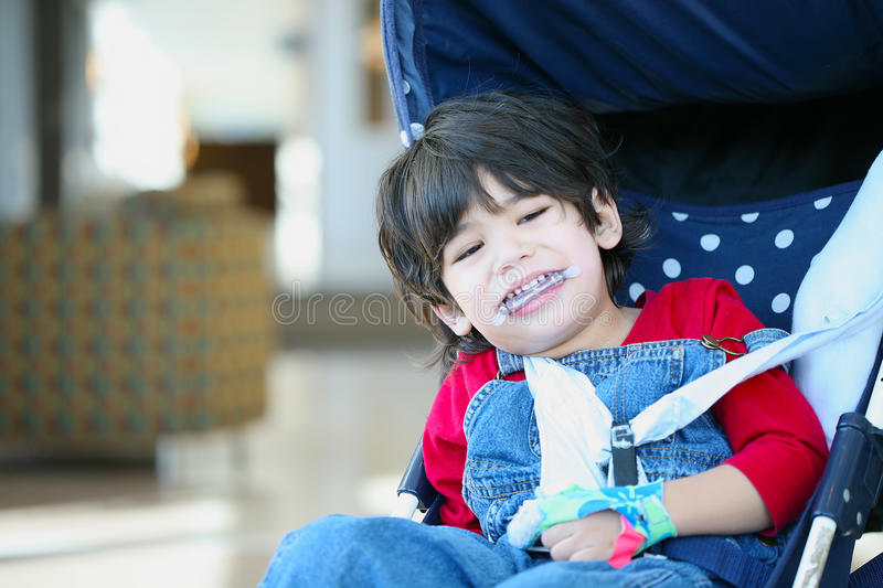 Disabled boy with cerebral palsy. Cute disabled boy with cerebral palsy smiling in stroller stock photography