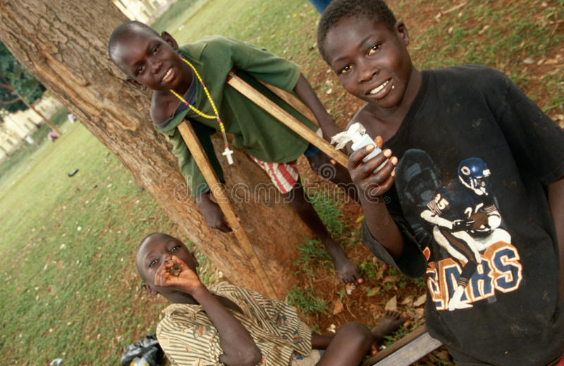 A disabled boy and glue sniffers in Kampala, Uganda stock images