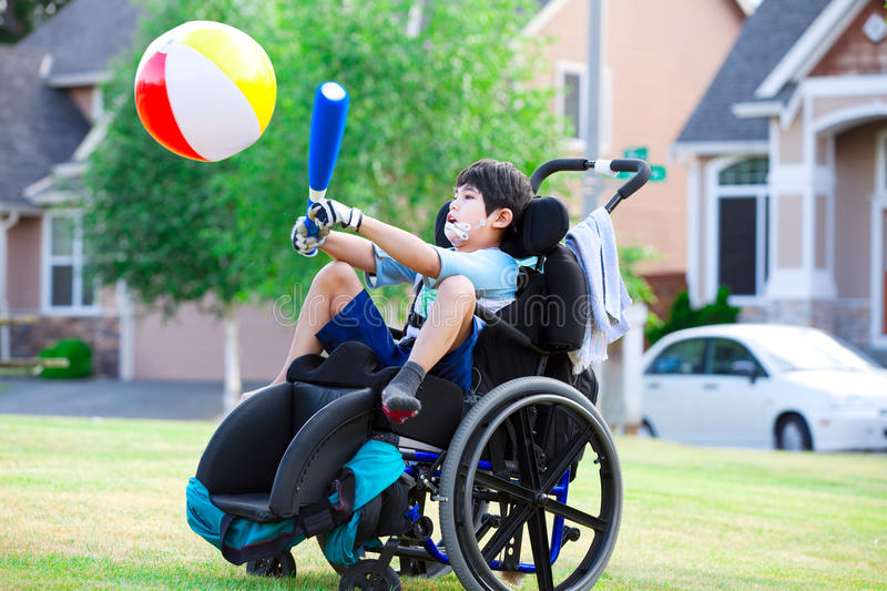 Disabled boy hitting ball with bat at park stock photography