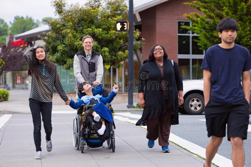 Disabled boy in wheelchair in city  with family and caregiver royalty free stock photos
