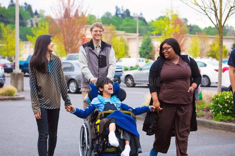 Disabled boy in wheelchair in city  with family and caregiver stock image