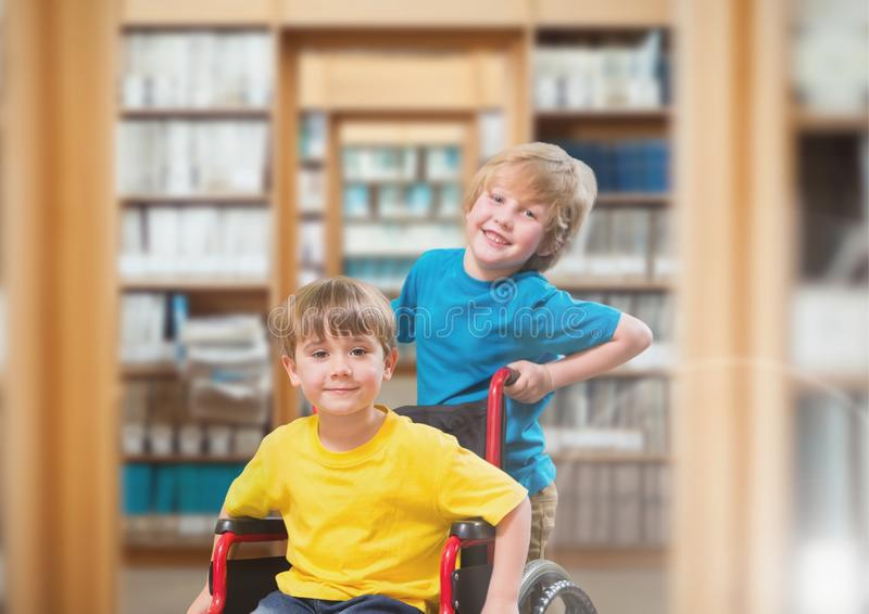 Disabled boy in wheelchair with friend in school library royalty free stock image