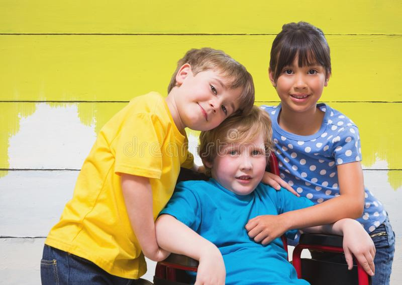 Disabled boy in wheelchair with friends with bright painted yellow wood background royalty free stock photography