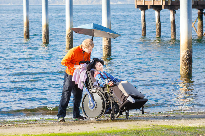 Disabled boy in wheelchair with his caregiver on beach royalty free stock photography