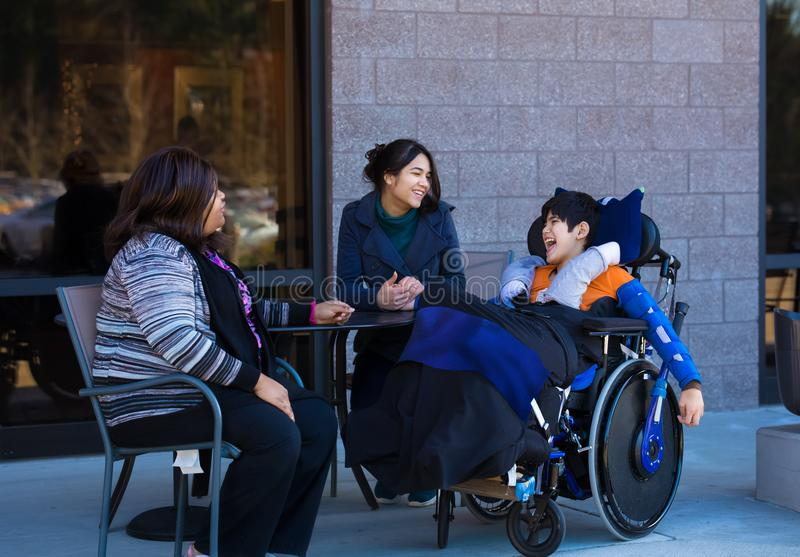 Disabled boy in wheelchair at table outdoors talking with caregivers royalty free stock photo