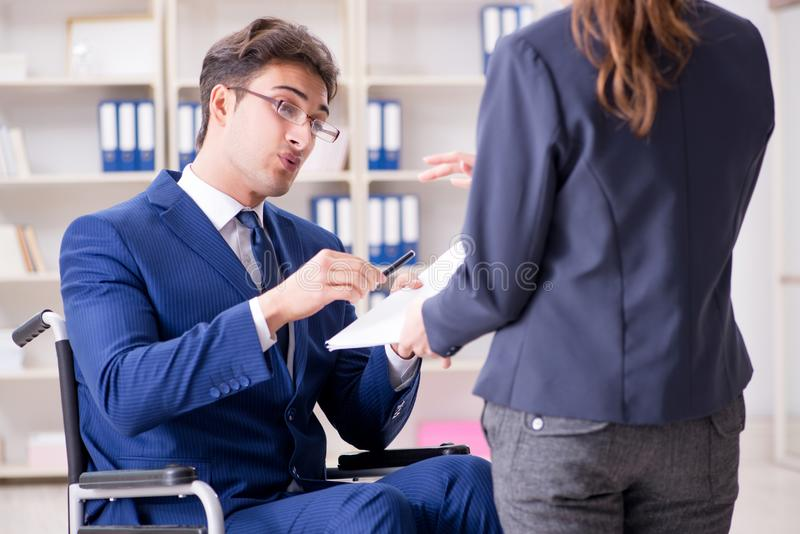 The disabled businessman having discussion with female colleague. Disabled businessman having discussion with female colleague royalty free stock images