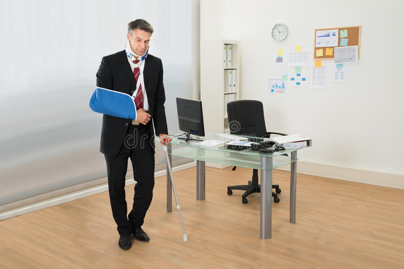 Disabled businessman standing with crutches. Portrait Of Disabled Businessman Standing With Crutches In Office royalty free stock photo