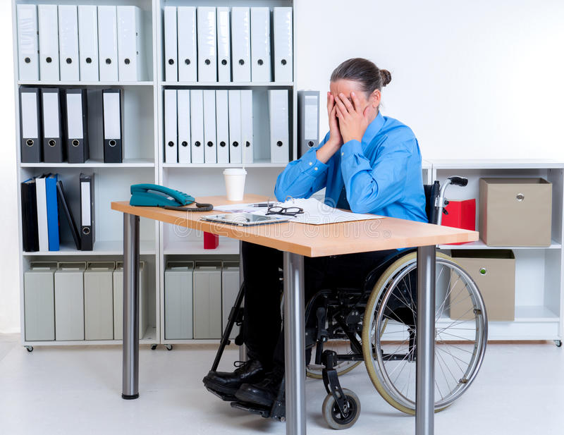 Disabled businessman in wheelchair is depressed stock photos