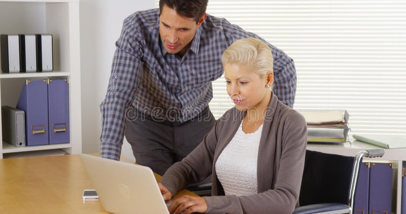 Disabled businesswoman and coworker working together on laptop royalty free stock image