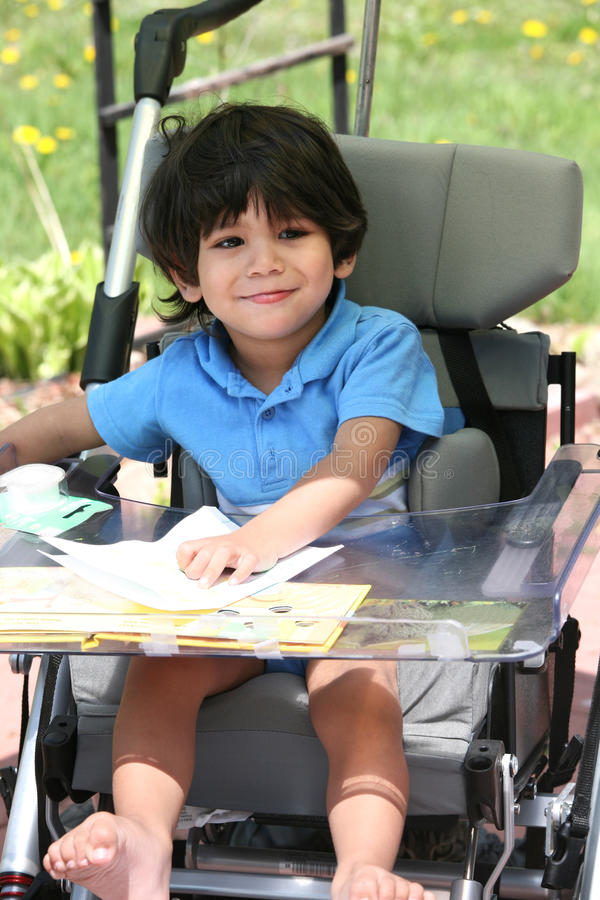 Disabled child in medical stroller stock photos