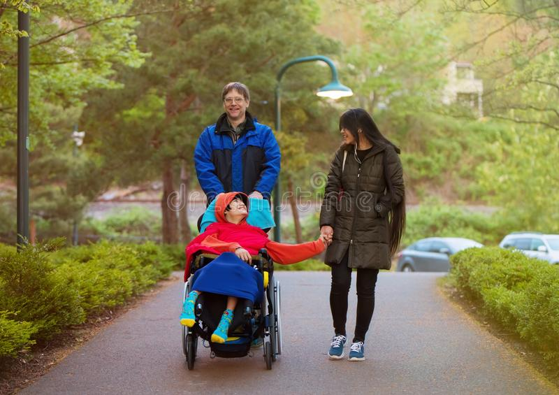 Disabled child in wheelchair at park with father and sister royalty free stock photos