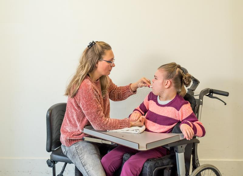 A disabled child in a wheelchair together with a voluntary care worker stock photography