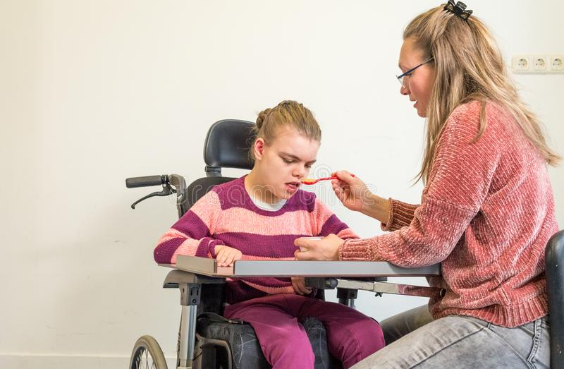 A disabled child in a wheelchair together with a voluntary care worker. A disabled child in a wheelchair being cared for by a voluntary care worker who is royalty free stock images
