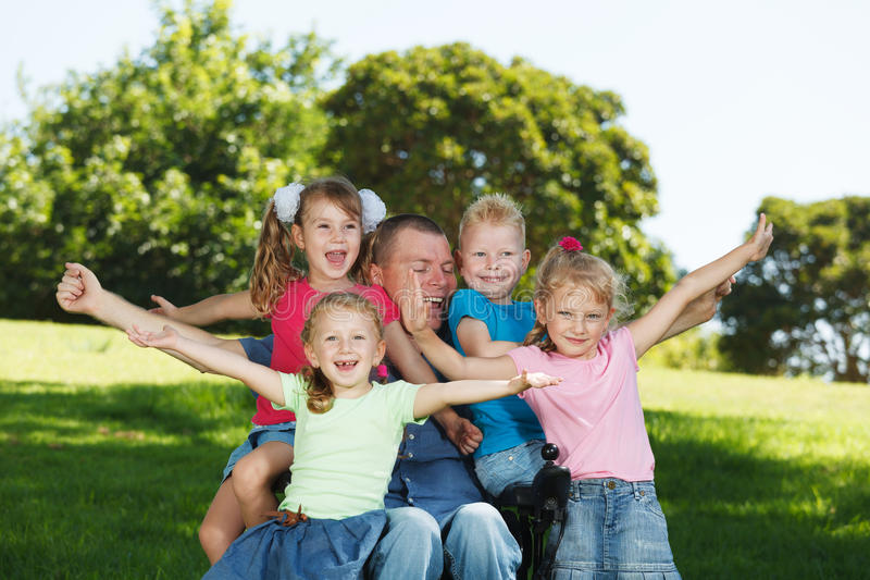 Disabled dad play with children royalty free stock image