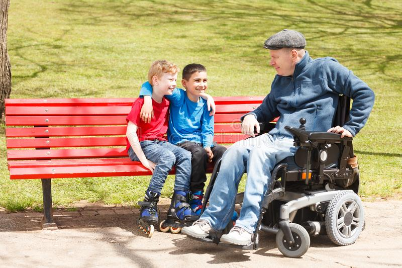 Disabled dad play with sons royalty free stock image
