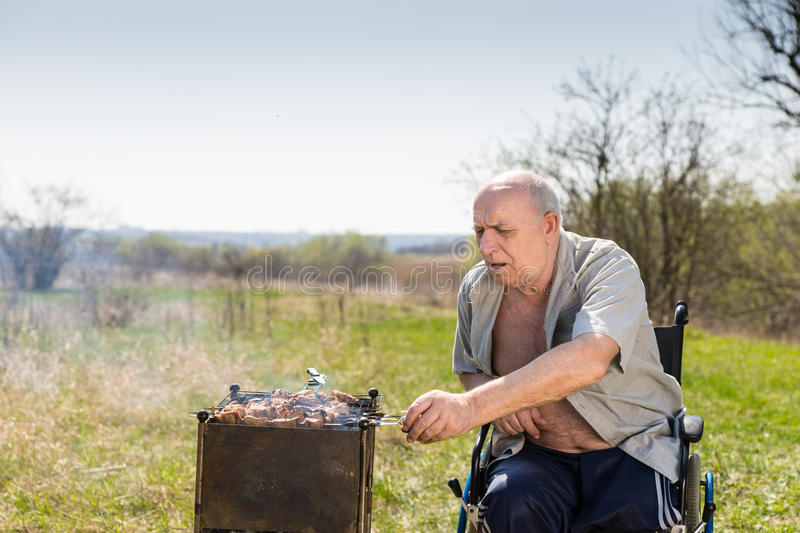 Disabled Elderly Man Grilling at the Park Alone. Disabled Elderly Man with Unbuttoned Shirt Sitting on his Wheelchair While Grilling Some Meat Sausages to Eat at royalty free stock image