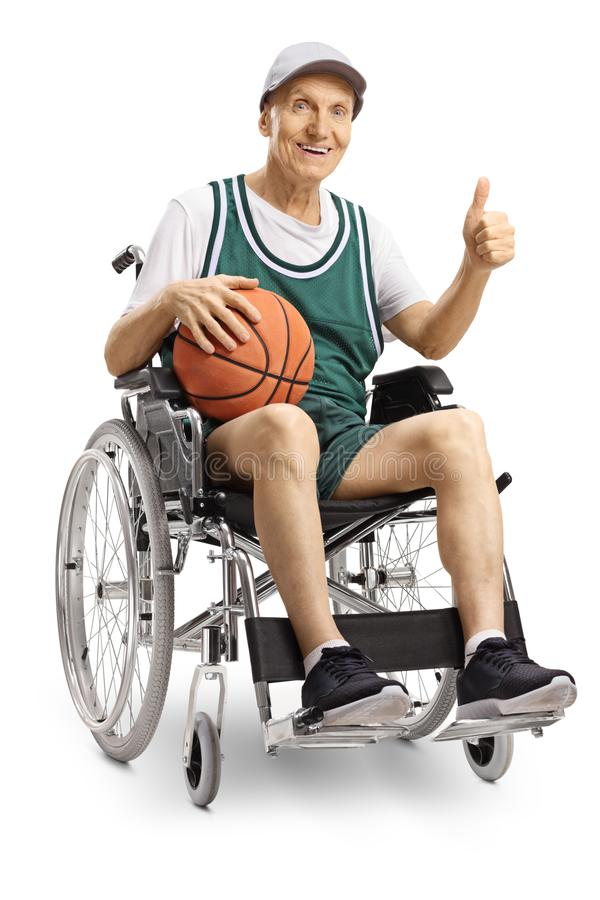Disabled elderly man in a wheelchair holding a basketball and showing thumbs up. Isolated on white background royalty free stock image