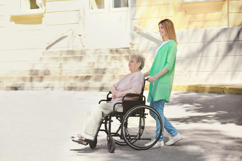 Disabled elderly woman and young caregiver outdoors. Disabled elderly women and young caregiver outdoors on sunny day royalty free stock photo