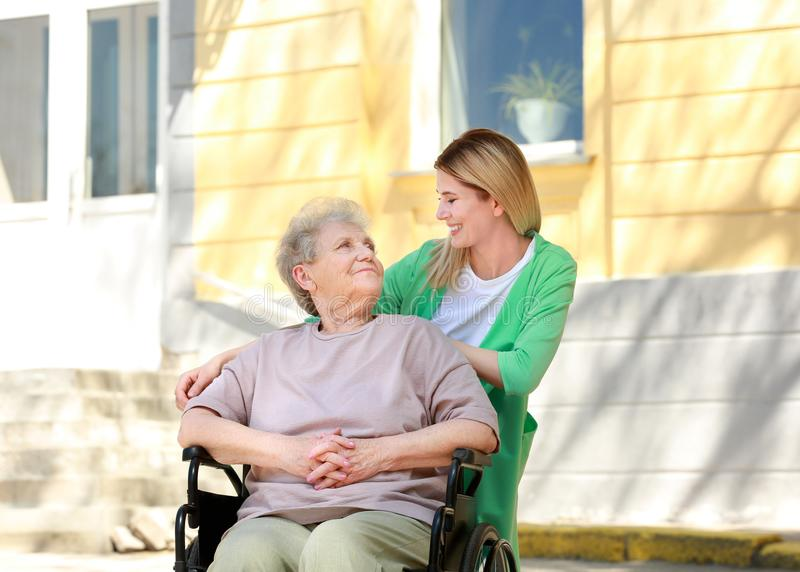 Disabled elderly woman and young caregiver outdoors. Disabled elderly women and young caregiver outdoors on sunny day royalty free stock image