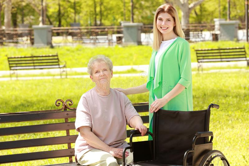Disabled elderly woman and young caregiver in park. Disabled elderly women and young caregiver in park on sunny day stock image