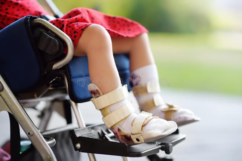 Disabled girl sitting in wheelchair. On her legs orthosis. Child cerebral palsy. Inclusion. Family with disabled kid stock images