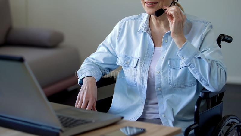 Disabled grandmother in headset talking with family online, video conference. Stock photo stock images