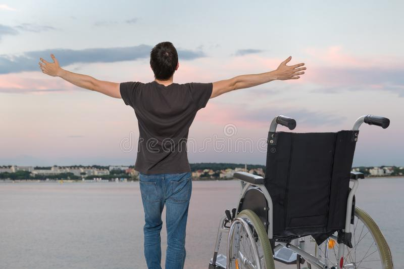 Disabled handicapped man is healthy again. He is happy and standing near his wheelchair. stock images