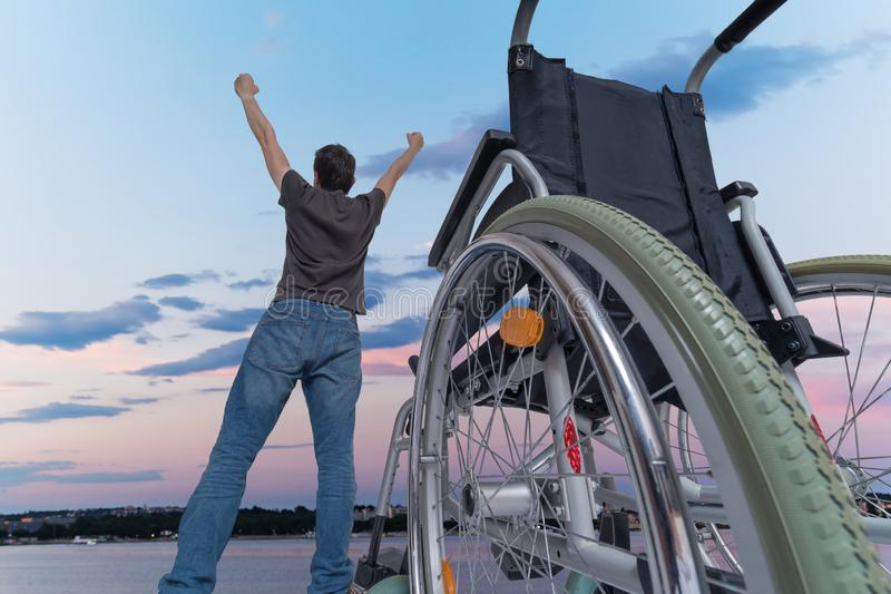 Disabled handicapped man is healthy again. He is happy and standing near his wheelchair. royalty free stock images