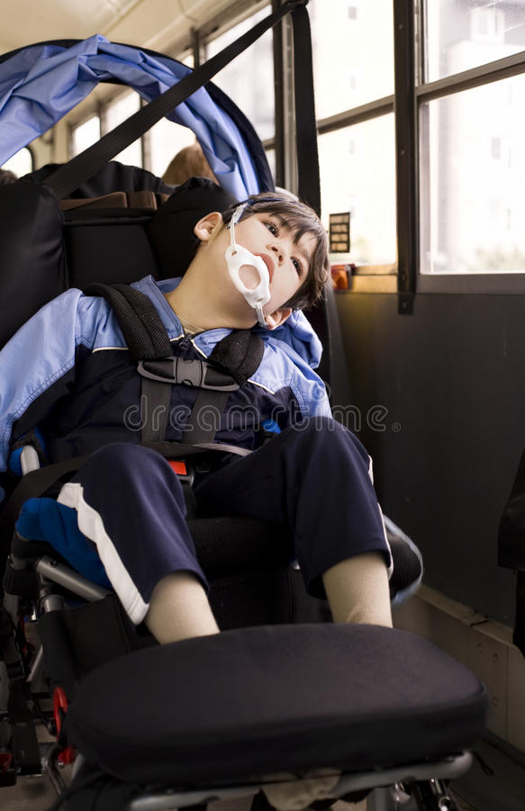 Disabled little boy in wheelchair on school bus stock images