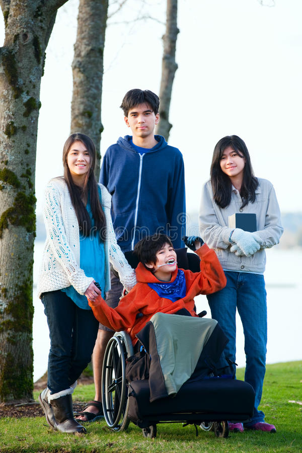 Disabled little boy in wheelchair surrounded by brother and sisters at lakeside. Child has cerebral palsy and children are all bi royalty free stock images