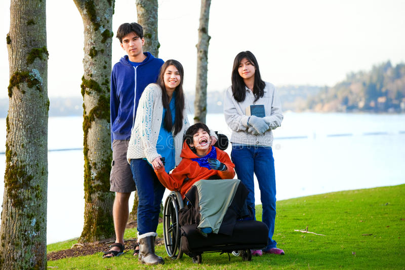 Disabled little boy in wheelchair surrounded by brother and sisters at lakeside. Child has cerebral palsy and children are all bi. Racial royalty free stock photography