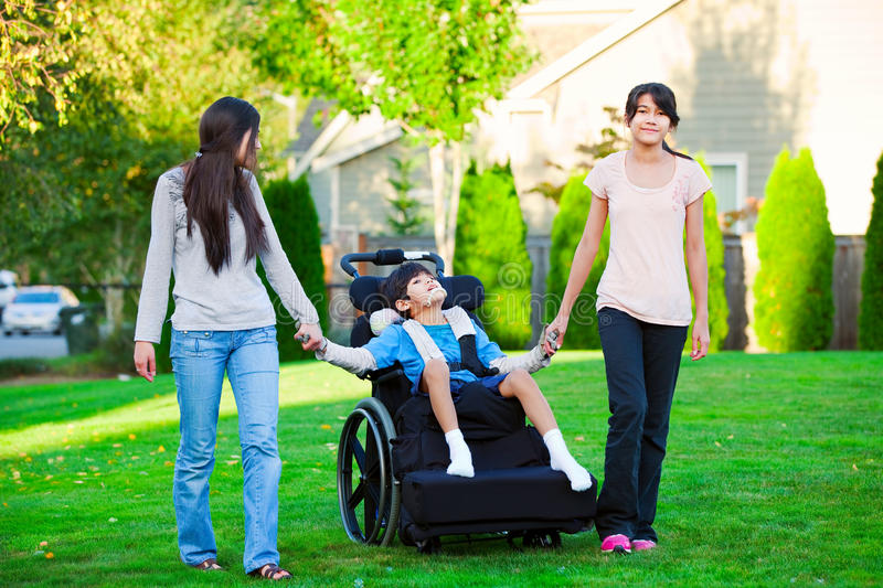 Disabled little boy in wheelchair walking with sisters on glassy royalty free stock photos