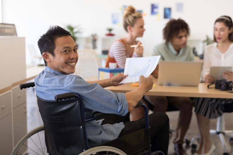 Disabled male executive holding graph paper in offce royalty free stock photography