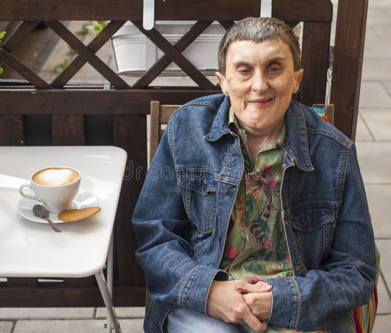 Disabled man with cerebral palsy sitting at outdoor cafe. Disabled man with cerebral palsy sitting at outdoor cafe with a cappuccino royalty free stock image