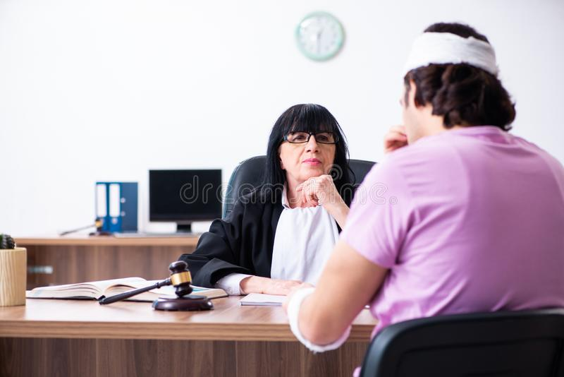 Disabled man consulting judge for damages litigation. The disabled men consulting judge for damages litigation royalty free stock images