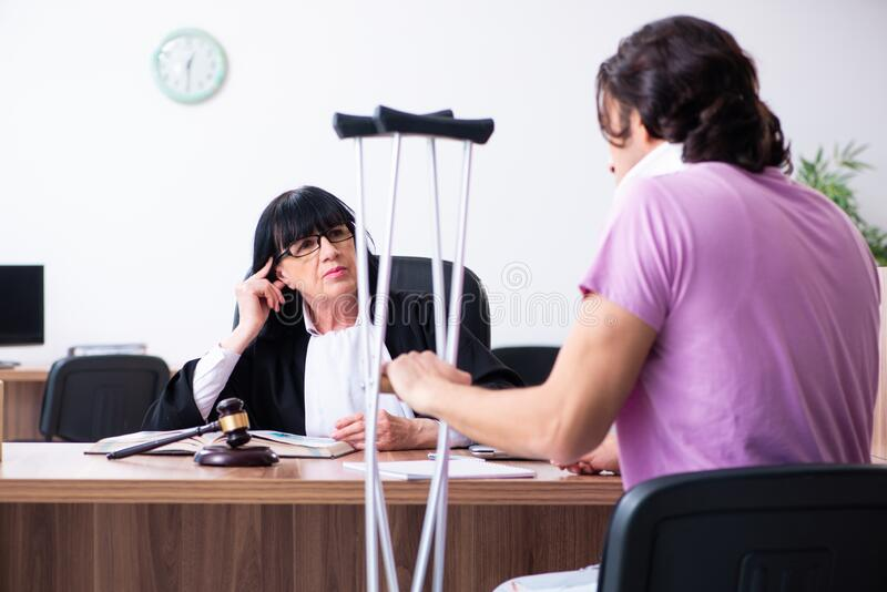 Disabled man consulting judge for damages litigation stock image
