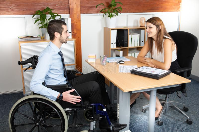 Disabled man having a business meeting with a businesswoman. A Disabled men having a business meeting with a businesswoman royalty free stock photography