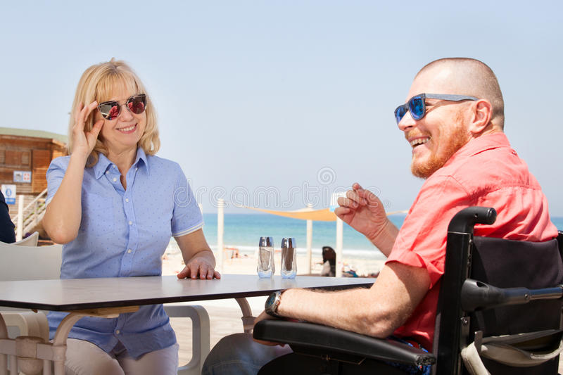 Disabled man with his wife having fun while sitting at the coffee bar near the beach royalty free stock image