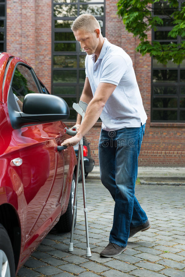 Disabled man holding crutches opening door of a car. Portrait Of A Handicapped Man With Crutches Opening Door Of A Car stock photos