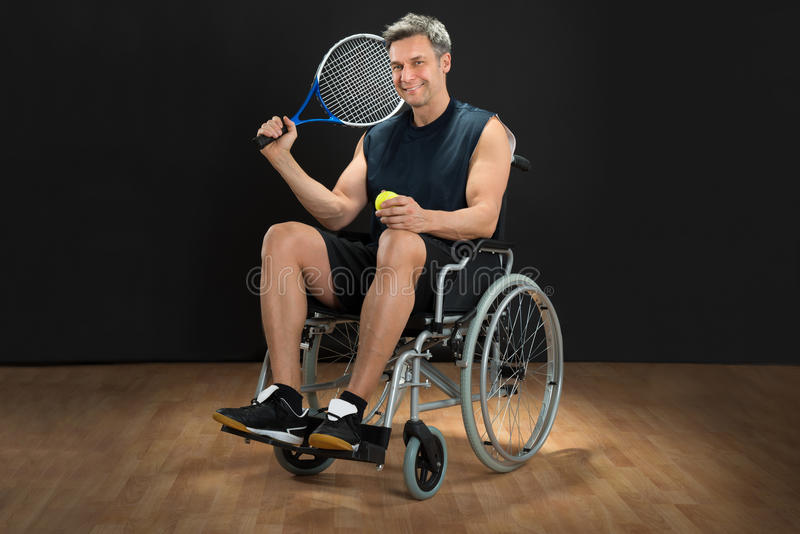 Disabled man holding racket and ball stock photography
