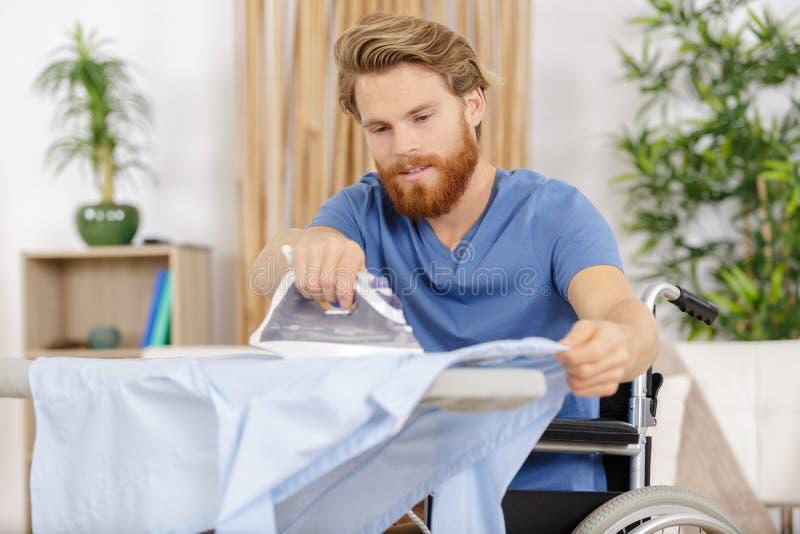 Disabled man ironing at home royalty free stock photo