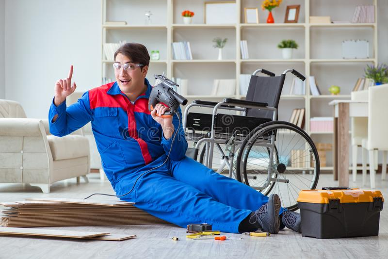 The disabled man laying floor laminate in office stock photos