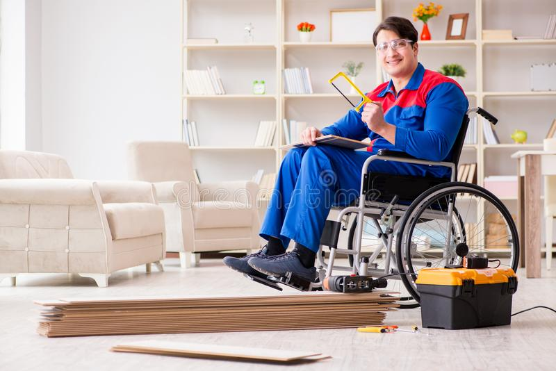 The disabled man laying floor laminate in office stock images