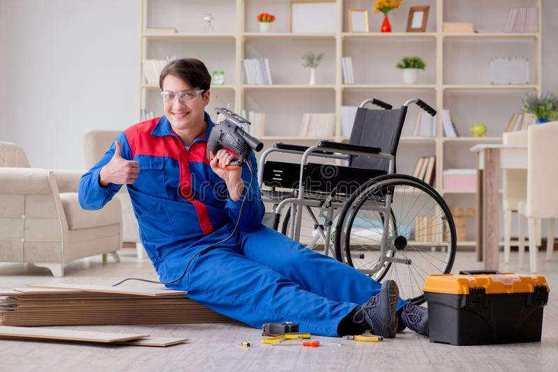 The disabled man laying floor laminate in office stock photo