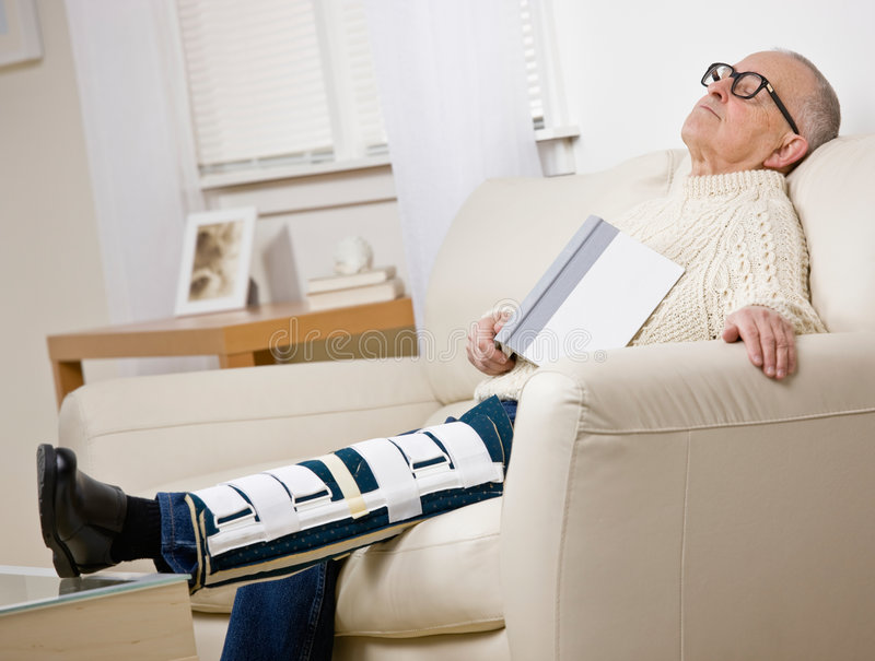 Disabled man with leg brace holding book stock image
