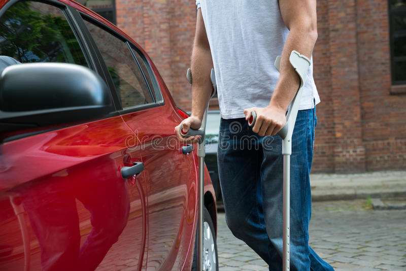 Disabled man opening door of a car. Close-up Of A Disabled Man With Crutches Opening Door Of A Car stock photos