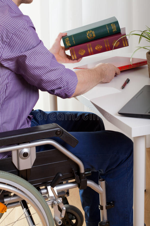 A disabled man sitting and learns. A disabled man sitting at a desk and learns stock image