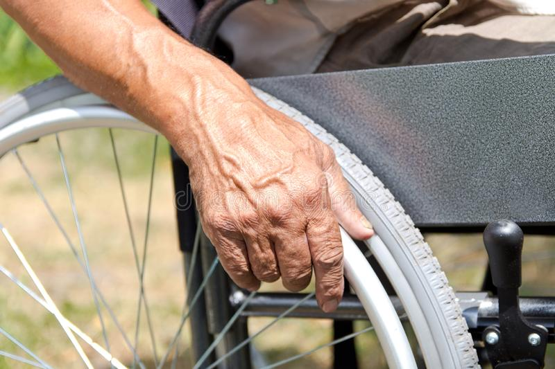 A disabled man is sitting in a wheelchair ,Holds his hands on the wheel. Handicap people Concept. Medical, mature, elderly, disability, happy, sick royalty free stock photography