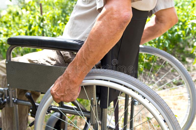 A disabled man is sitting in a wheelchair ,Holds his hands on the wheel. Handicap people Concept. Medical, mature, elderly, disability, happy, sick stock photography