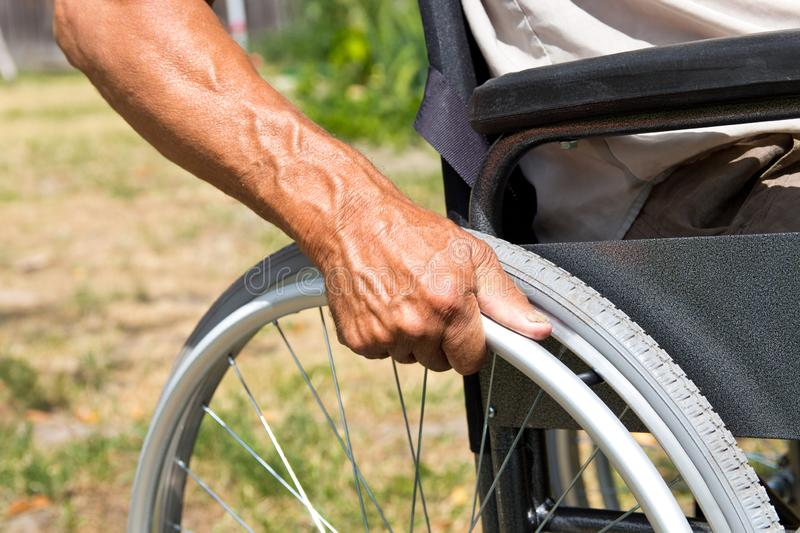 A disabled man is sitting in a wheelchair ,Holds his hands on the wheel. Handicap people Concept. Medical, mature, elderly, disability, happy, sick royalty free stock image
